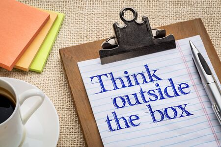 unorthodox: think outside the box - motivational slogan on a clipboard with a cup of coffee Stock Photo