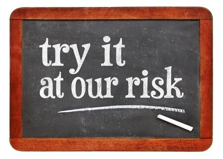 try at out risk marketing slogan - white chalk text on a vintage slate blackboard Stock Photo