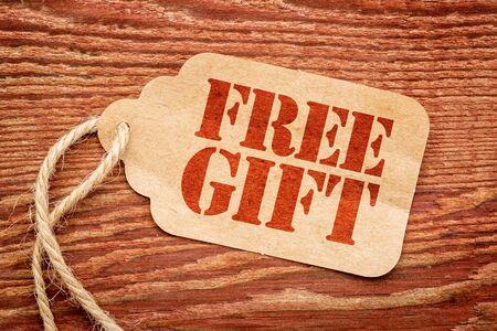 gratis geschenk teken - rode stencil tekst een papieren prijskaartje tegen rustieke houten