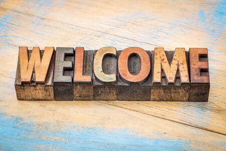 bienvenida: Palabra de bienvenida resumen - texto en la cosecha de tipografía de madera bloques de tipo manchado por las tintas de color contra el grunge de madera pintada Foto de archivo