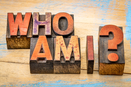 Who am I - a philosophical question spelled in vintage letterpress wood type printing blocks against grunge, painted wood Stockfoto