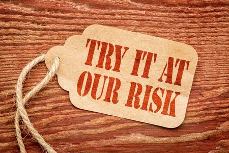 Try it at our risk - red stencil text on a paper price tag against rustic wood Stock fotó