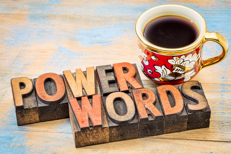 power words - text in vintage letterpress wood type printing blocks against painted wood with a cup of coffee