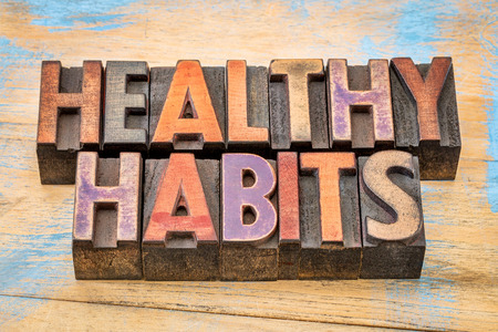 habitos saludables: hábitos saludables palabras en bloques de impresión de tipo madera de tipografía contra la madera pintada