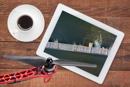diversion: aerial landscape photography concept - reviewing aerial pictures of  a river diversion dam on a digital tablet with a drone propeller in foreground, screen picture copyright by the photographer