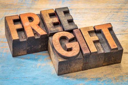 free gift: free gift words in vintage letterpress wood type printing blocks against painted wood