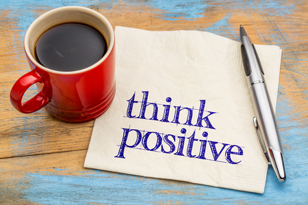 think positive - mindset concept on a napkin with a cup of coffee against grunge wood