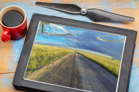 aerial landscape photography concept - reviewing aerial pictures of  a prairie in Colorado on a digital tablet with a drone propeller and coffee, screen picture copyright by the photographer Stock Photo