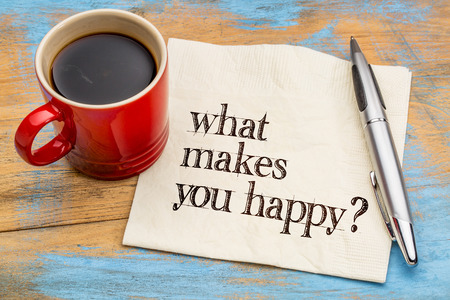 What makes you happy? A question handwritten on a napkin with a cup of coffee against grunge wood