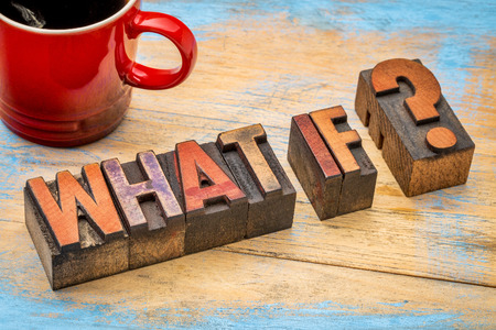 what if question in vintage letterpress wood type blocks against grunge, painted wood with a cup of coffee Archivio Fotografico