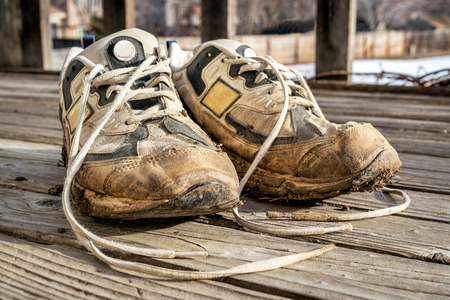 muddy: a pair of old muddy running shoes against wooden deck Stock Photo