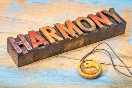 harmony word in vintage letterpress wood type with ying and yang symbol pendant