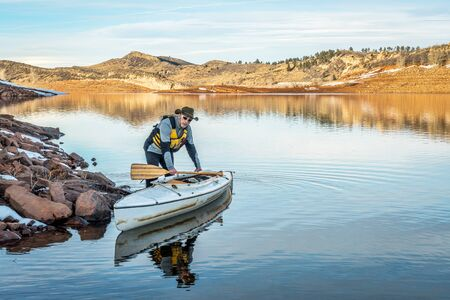 horsetooth reservoir: senior male paddler with his decked expedition canoe on a shore  of Horsetooth Reservoir near Fort Collins in northern Colorado, winter scenery