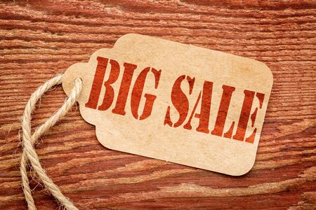 big sale sign - a paper price tag against rustic red painted barn wood - shopping concept