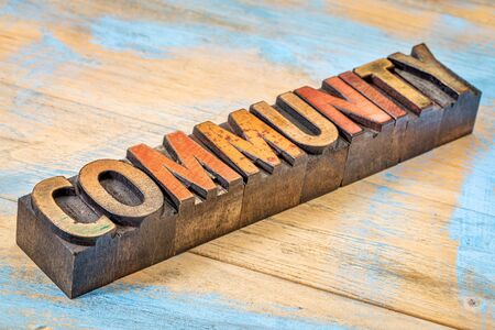 community banner -word abstract in vintage letterpress wood type stained by inks against grunge painted wood