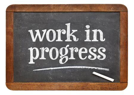 work in progress  - white chalk text on a vintage slate blackboard