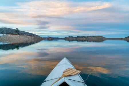 horsetooth reservoir: Horsetooth Reservoir near Fort Collins in northern Colorado, bow view from a decked expedition canoe with a wooden paddle, winter scenery at dusk
