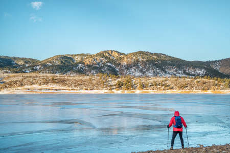 horsetooth reservoir: male hiker at a shore of frozen Horsetooth Reservoir near Fort Collins, Colorado  with Athurss Rock in background