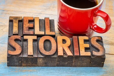 tell stories word abstract - text in vintage letterpress wood type with a cup of coffee - storytelling concept