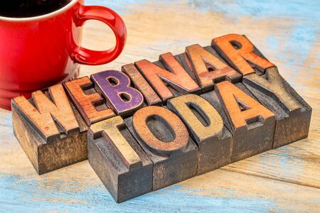 webinar today sign  - text in vintage letterpress wood type against grunge painted wood with a red cup of coffee Stock Photo