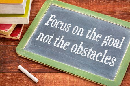 Focus on the goal, not the obstacles - inspirational advice on a slate blackboard with a white chalk and a stack of books against rustic wooden table