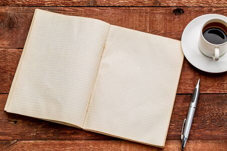 old blank notebook opened on a  red barn wood table with a cup of coffee Stock Photo