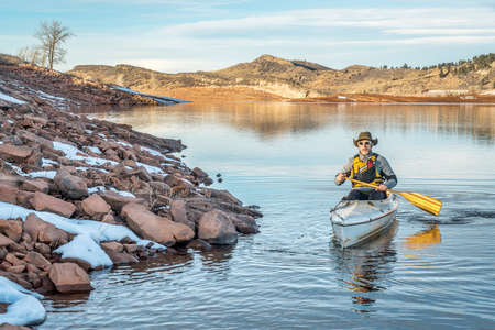 paddling: senior male paddling a decked expedition canoe on Horsetooth Reservoir near Fort Collins in northern Colorado, winter scenery
