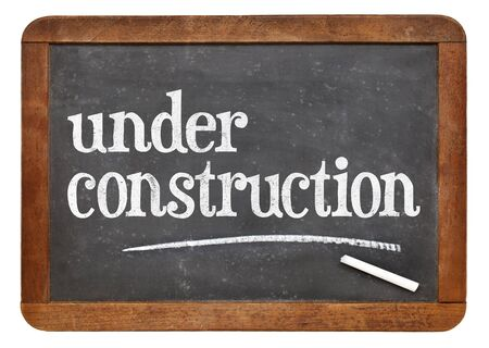 under construction sign - white chalk text  on a vintage blackboard isolated on white