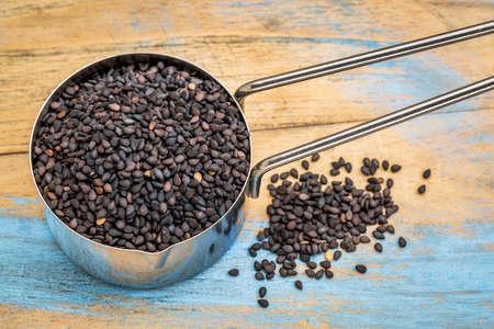 black sesame seeds in a measuring metal scoop a grunge painted wood