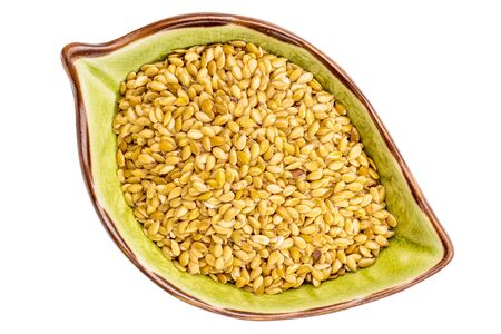 golden flax seeds on an isolated leaf shaped ceramic bowl, top view