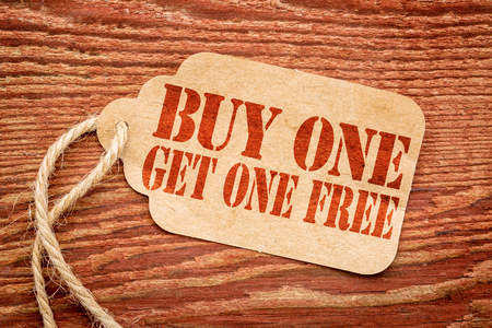 buy one: buy one get one free sale sign - a paper price tag against rustic red painted barn wood - shopping concept