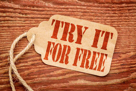 Try it for free  offer  - red stencil text on a paper price tag against rustic wood