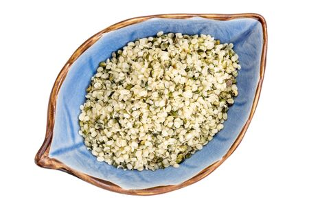 hemp hemp seed: hemp seed hearts on an isolated leaf shaped ceramic bowl, top view