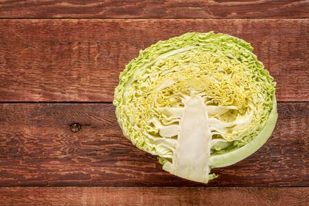 half of green savoy cabbage on red barn wood table with a copy space