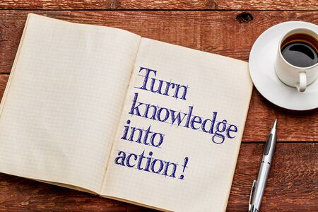 Turn knowledge into action! Motivational words in an old notebook with a cup of coffee Stock Photo