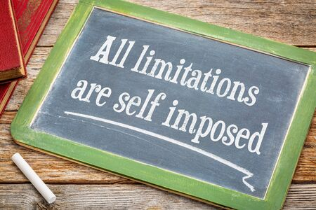 all limitations are self imposed - inspirational statement on a  blackboard with a white chalk and a stack of books against rustic wooden table Stock Photo