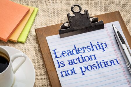 Leadership is action, not position -  reminder on a clipboard with a cup of coffee