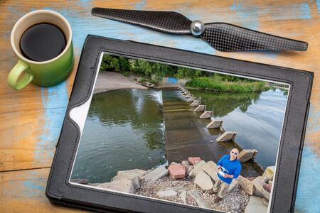 aerial photography concept - reviewing aerial picture (drone operator on a river shore) on a digital tablet with a drone rotor propeller and a cup of coffee