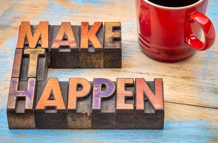 Make it happen motivational slogan - text in vintage letterpress wood type against grunge painted wood with a cup of coffee Stock Photo