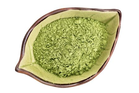 organic barley grass powder on an isolated leaf shaped ceramic bowl, top view