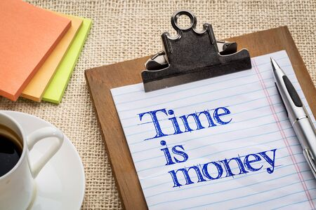 time is money reminder  - motivational slogan on a clipboard with a cup of coffee Stock Photo
