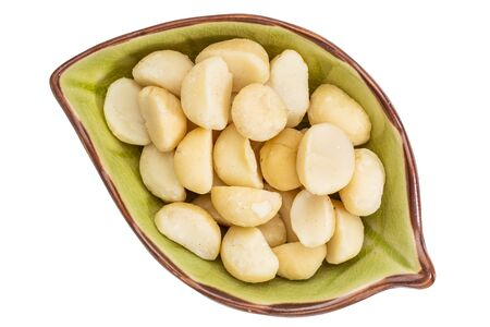 macadamia nuts  in an isolated leaf shaped ceramic bowl, top view