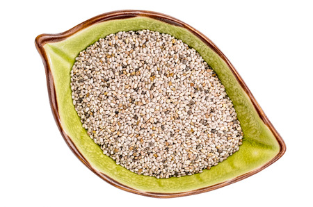 white chia: white chia seeds (Salvia Hispanica) in a ceramic leaf shaped bowl isolated on white, top view