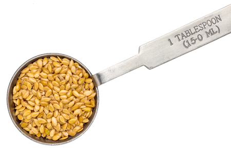 golden flax seed seed on metal measuring tablespoon, isolated on white Stock Photo