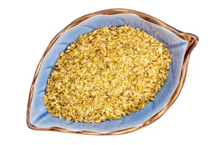 golden flax meal in a leaf shaped ceramic bowl isolated on white