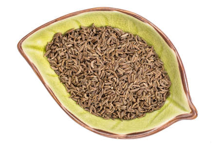 caraway seeds on an isolated leaf shaped ceramic bowl, top view Stock Photo