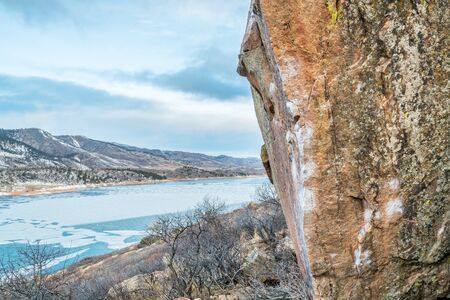 horsetooth reservoir: climbing wall with white chalk marks over Horsetooth Reservoir, Rotary Park, Fort Collins, Colorado, winter scenery with ice on a lake