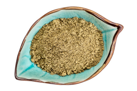 hemp hemp seed: hemp seed  protein powder on an isolated leaf shaped ceramic bowl, top view