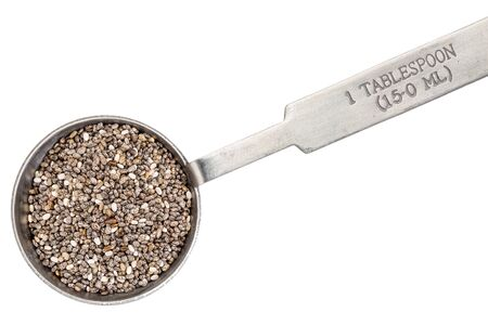 chia seed on metal measuring tablespoon, isolated on white Stock Photo