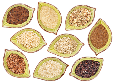 nine gluten free grains (black quinoa, buckwheat, amaranth, teff, sorghum, kaniwa, millet, and brown rice) - top view of leaf shaped ceramic bowls isolated on white Stock Photo